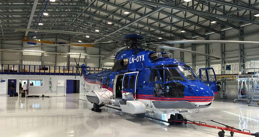 A blue large helicopter parked inside a steel, clean, easy to access and maintain metal hangar.