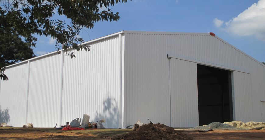 Exterior of a white Frisomat metal hall with large door.